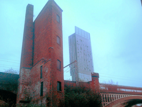 Old brick warehaouse with Hilton Hotel glass tower in background