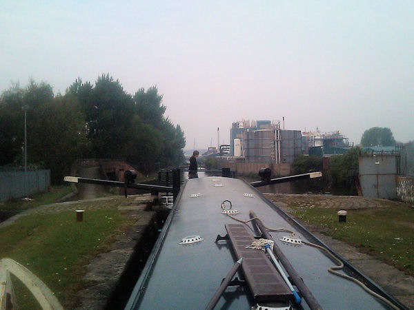 Narrowboat in lock in industrial setting