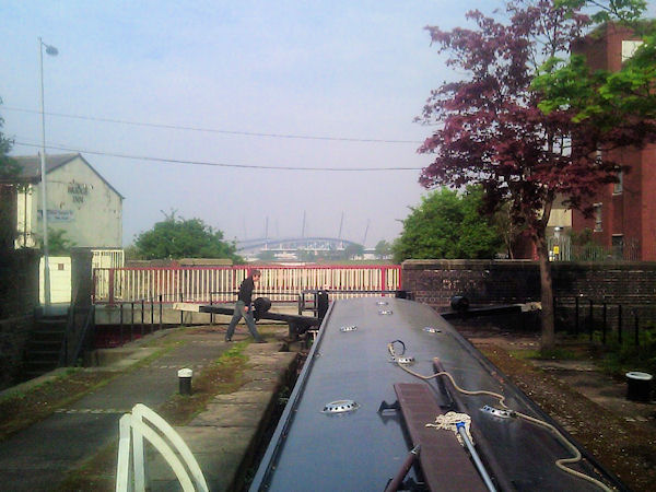 Narrowboat in lock with Manchester City stadium visible in background