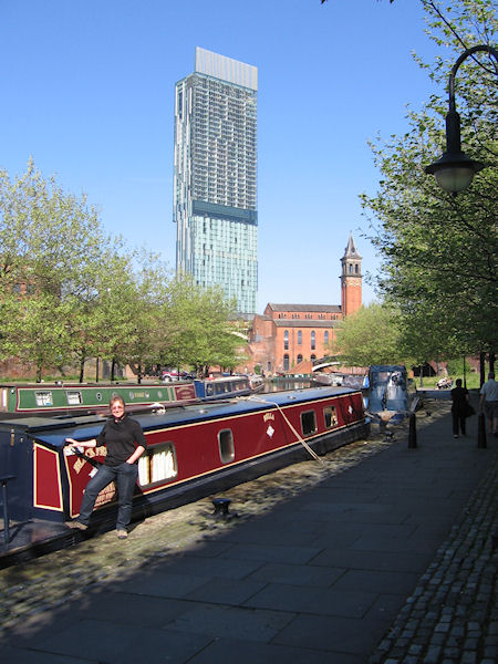 Woman stood by moored narrowboat with Hilton Hotel Manchester in background