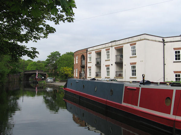 Narrowboat moored outside two storey apartments